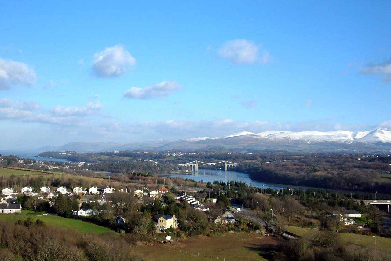 A panoramic view from Anglesey Column - with the suspension bridge and a snow-capped Snowdonia