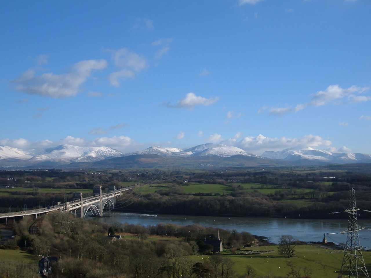 The Tubular Bridge and a snow-capped Snowdonia from the Anglesey Column